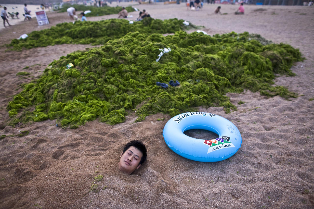 A tourist from Tianjin is covered with sand as he rests next to a pile of algae on a beach in Qingdao, Shandong province July 7, 2008.  Thousands of Chinese troops and volunteers should clear unsightly algae from competition areas at the Qingdao Olympic sailing venue by Thursday, an official said.  REUTERS/Nir Elias