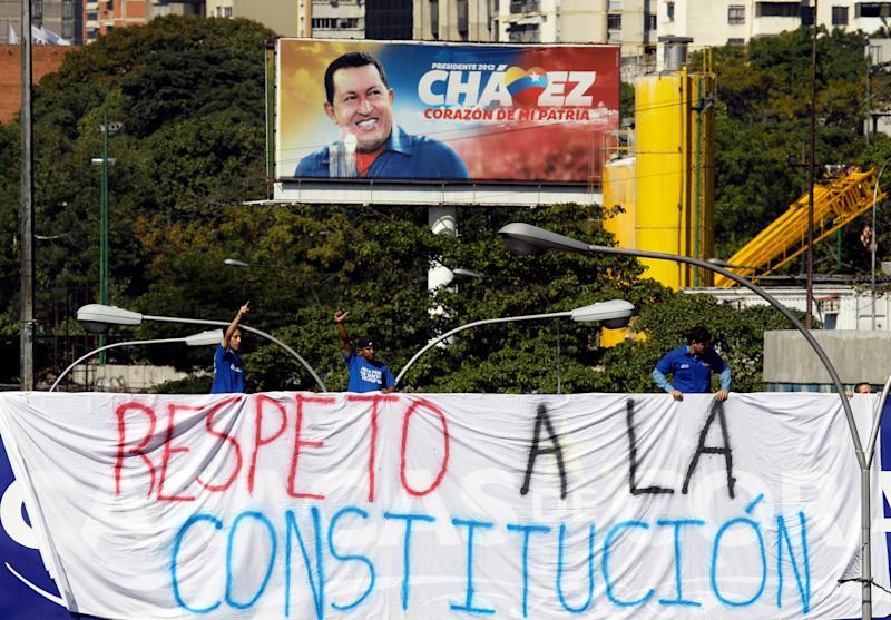 """University students hang a banner that reads in Spanish: """"Respect the constitution,"""" over the side of a bridge near a billboard showing President Hugo Chavez in Caracas, Venezuela, Wednesday, Jan. 16, 2013. Vice President Nicolas Maduro took the place of the ailing Venezuelan president on Tuesday by delivering a short speech and turning in a state-of-the-nation report amid legal debate about his legitimacy. (AP Photo/Fernando Llano)"""
