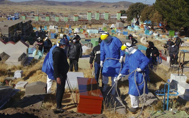 Funerary employees in protective suits prepare to lower the coffin into the ground during the burial of a COVID-19 victim at the local cemetery in the remote Aymara highland village of Acora, one hour away from the city of Puno, close to the border with Bolivia - CARLOS MAMANI/AFP via Getty Images