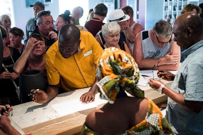A Thomas Cook travel representative helps tourists prepare to leave the Gambia after the British Government changed the travel advisory to amber due to the state of emergency in the country on January 18, 2017 (AFP Photo/)
