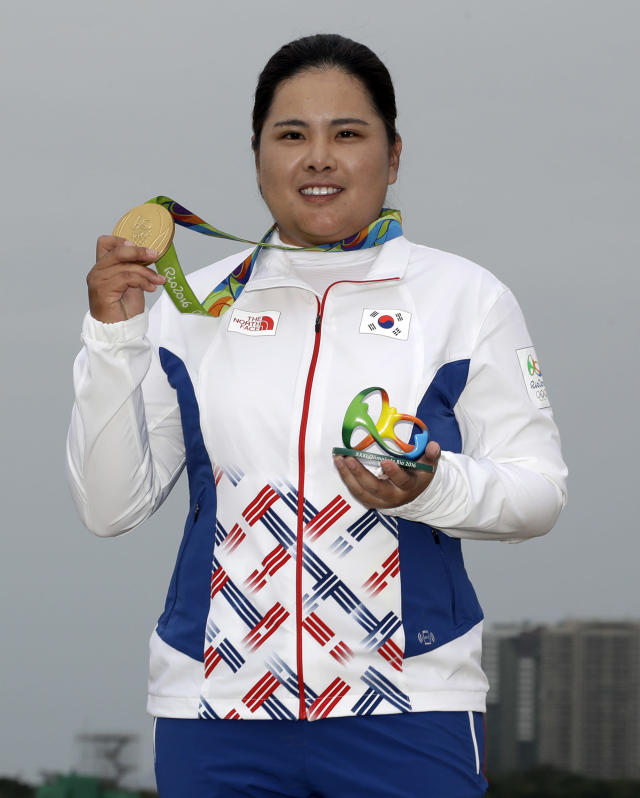 FILE - In this Aug. 20, 2016, file photo, Inbee Park, of South Korea, holds up her gold medal after the final round of women's golf at the Summer Olympics in Rio de Janeiro, Brazil. With the postponement of the Tokyo Games, Park gets more time to try to boost her world ranking and try to defend her gold medal in 2021. (AP Photo/Chris Carlson, File)