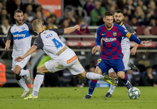 Barcelona's Lionel Messi, left, drives the ball during a Spanish La Liga soccer match between Barcelona and Alaves at Camp Nou stadium in Barcelona, Spain, Saturday, Dec. 21, 2019. (AP Photo/Joan Monfort)