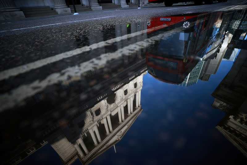 FILE PHOTO: The Bank of England and the City of London financial district are reflected in a puddle, in London