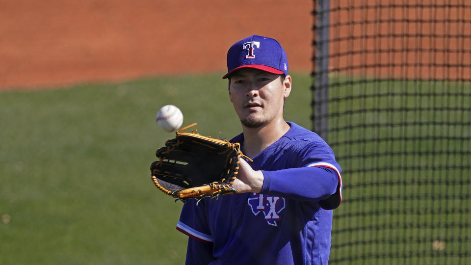 Texas Rangers pitcher Kohei Arihara, from Japan, catches a ball during spring training baseball practice Wednesday, Feb. 24, 2021, in Surprise, Ariz. (AP Photo/Charlie Riedel)