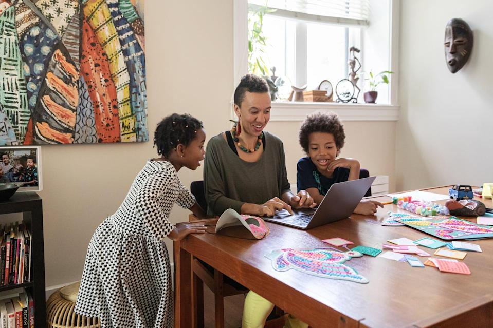 A woman sits with her son and daughter at a dining room table covered in craft materials