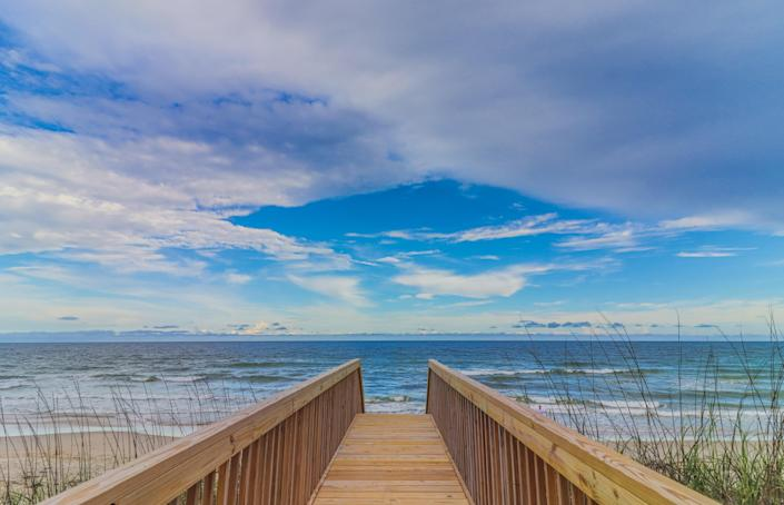 """Topsail is a long, thin stretch of land just south of Marine Corps Base Camp Lejeune (you'll know it and feel it, seeing F-15s make training runs up and down the coast). The shape gives it beach on both sides, whether you want the Atlantic waters perfect for swimming and <a href=""""https://www.cntraveler.com/story/complete-guide-to-family-travel?mbid=synd_yahoo_rss"""" rel=""""nofollow noopener"""" target=""""_blank"""" data-ylk=""""slk:playing with the kids"""" class=""""link rapid-noclick-resp"""">playing with the kids</a> or the calmer inlet prime for kayaking and fishing. The beach town of Surf City is home to a number of restaurants of all types to satisfy the appetite after a long day on the beach. Just remember: Pronounce it """"top-sull,"""" or you'll be swiftly corrected."""