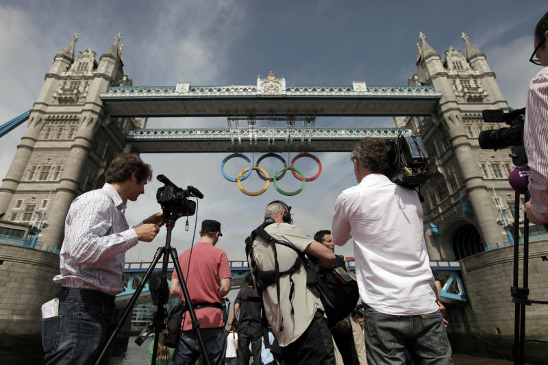 Members of the media photograph the Olympic rings atop the iconic Tower Bridge in London, after they were lowered into position, coinciding with one month to go until the start of London 2012 Games, Wednesday, June 27, 2012. The giant rings, which are fully retractable to allow for tall ships to pass through the bridge, will remain in position for the duration of the Games. (AP Photo/Lefteris Pitarakis)