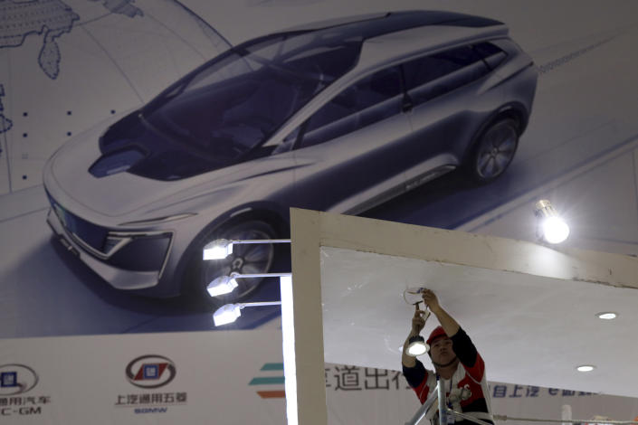 In this April 15, 2019, photo, an electrician installs lights at the Auto Shanghai 2019 show in Shanghai. China's electric car sales are stalling following the end of multibillion-dollar subsidies that made it the biggest market for the technology. Communist leaders want to make China a leader in electric cars but are shifting the burden to the industry by imposing mandatory sales quotas. (AP Photo/Ng Han Guan)