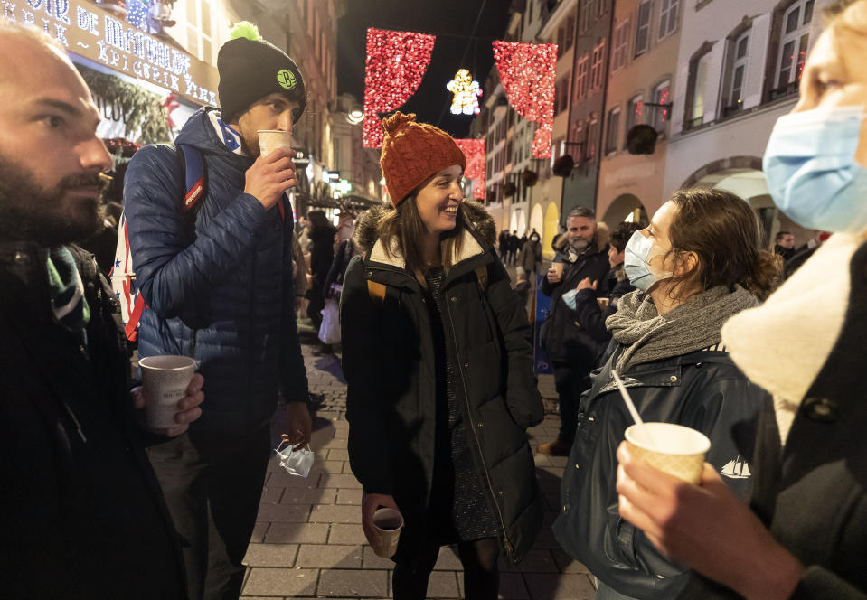FILE - In this Dec. 17, 2020 file photo, people enjoy a glass of mulled wine in the street before the curfew in Strasbourg, eastern France. Trying to fend off the need for a third nationwide lockdown that would further dent Europe's second-largest economy and put more jobs in danger, France is instead opting for creeping curfews. (AP Photo/Jean-Francois Badias, File)