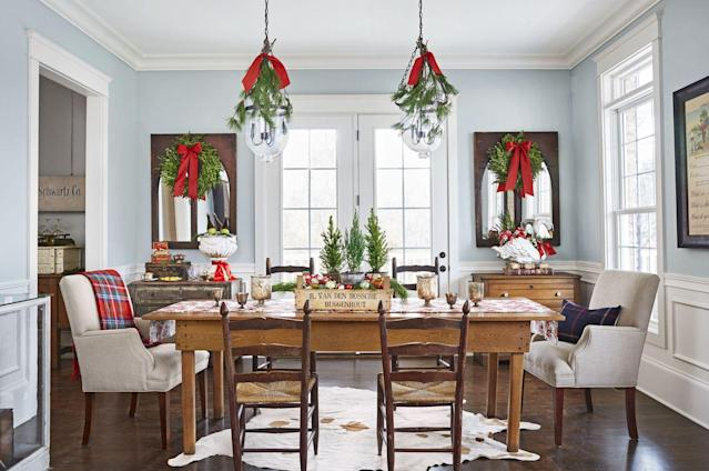 """<p>A weathered wood crate centerpiece brings good tidings to the room, while greenery hangs above the table and mirrors.</p><p><a href=""""https://www.amazon.com/s/ref=nb_sb_noss?url=search-alias%3Dgarden&field-keywords=christmas+garland"""" rel=""""nofollow noopener"""" target=""""_blank"""" data-ylk=""""slk:SHOP GARLAND"""" class=""""link rapid-noclick-resp"""">SHOP GARLAND</a><br></p>"""