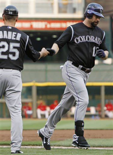 Colorado Rockies' Todd Helton (17) is congratulated by third base coach Rich Dauer (25) after Helton hit a two-run home run against the Cincinnati Reds in the second inning of a baseball game, Friday, May 25, 2012, in Cincinnati. (AP Photo/Al Behrman)