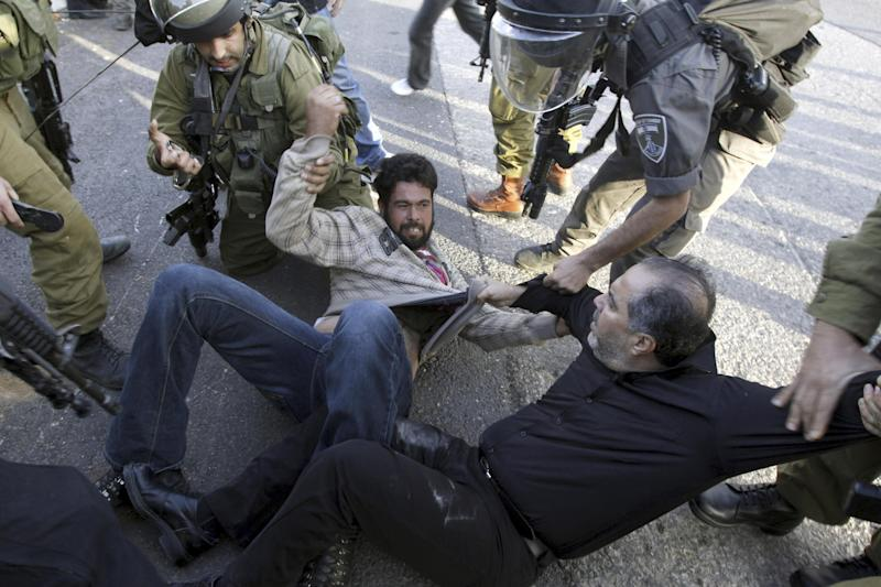 Israeli security forces detain Palestinians during clashes in the West Bank village of Anin, Saturday, Jan. 26, 2013. Hundreds of Palestinians clashed with Israeli security during a rally in support of Palestinians in Israeli jails. (AP Photo/Mohammed Ballas)