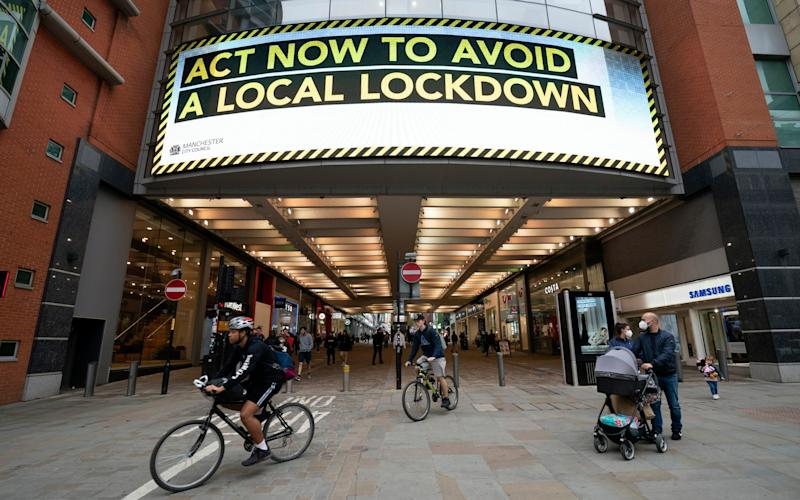 A sign in Manchester warns residents of the threat of tightening restrictions - Jon Super/AP