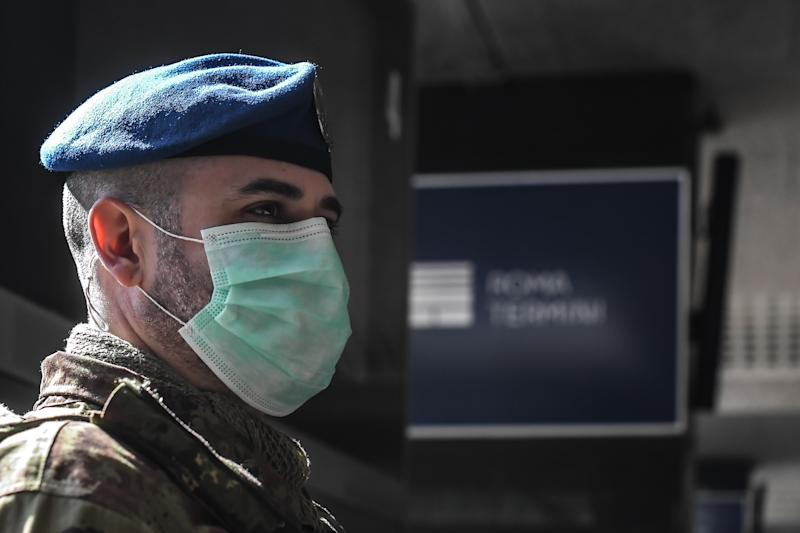 A soldier wearing a respiratory mask supervises platform access at the Termini railway station in Rome on March 10, 2020. - Italy imposed unprecedented national restrictions on its 60 million people on March 10, 2020 to control the deadly coronavirus, as China signalled major progress in its own battle against the global epidemic. (Photo by Tiziana FABI / AFP) (Photo by TIZIANA FABI/AFP via Getty Images)