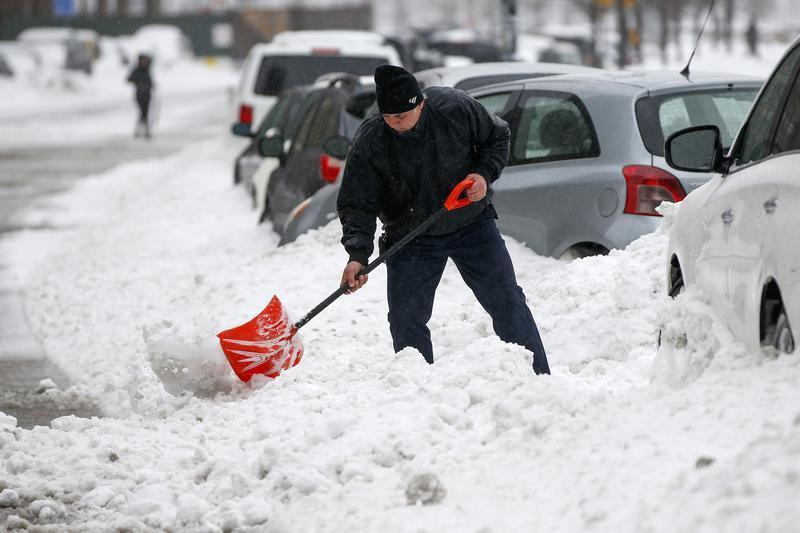 A man shovels snow in the Queens borough of New York