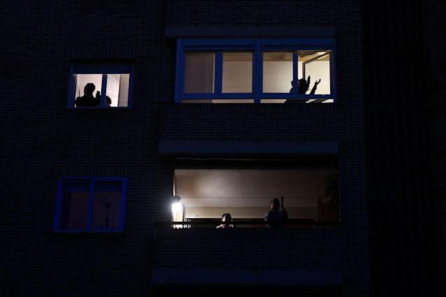Varios vecinos aplauden al personal sanitario como cada noche desde sus balcones en Madrid (Photo by PIERRE-PHILIPPE MARCOU / AFP) (Photo by PIERRE-PHILIPPE MARCOU/AFP via Getty Images)