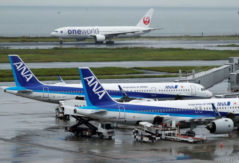 A Japan Airlines (JAL) aircraft takes off near All Nippon Airways (ANA) aircrafts, amid the coronavirus disease (COVID-19) outbreak at Haneda Airport in Tokyo