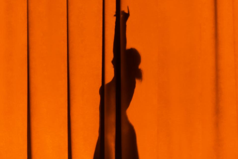 Female silhouette on the curtain. The shadow of a girl dancing on colored canvases.