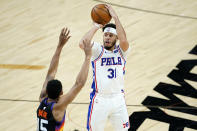 Philadelphia 76ers guard Seth Curry (31) shoots over Phoenix Suns guard Cameron Payne (15) during the first half of an NBA basketball game, Saturday, Feb. 13, 2021, in Phoenix.(AP Photo/Matt York)