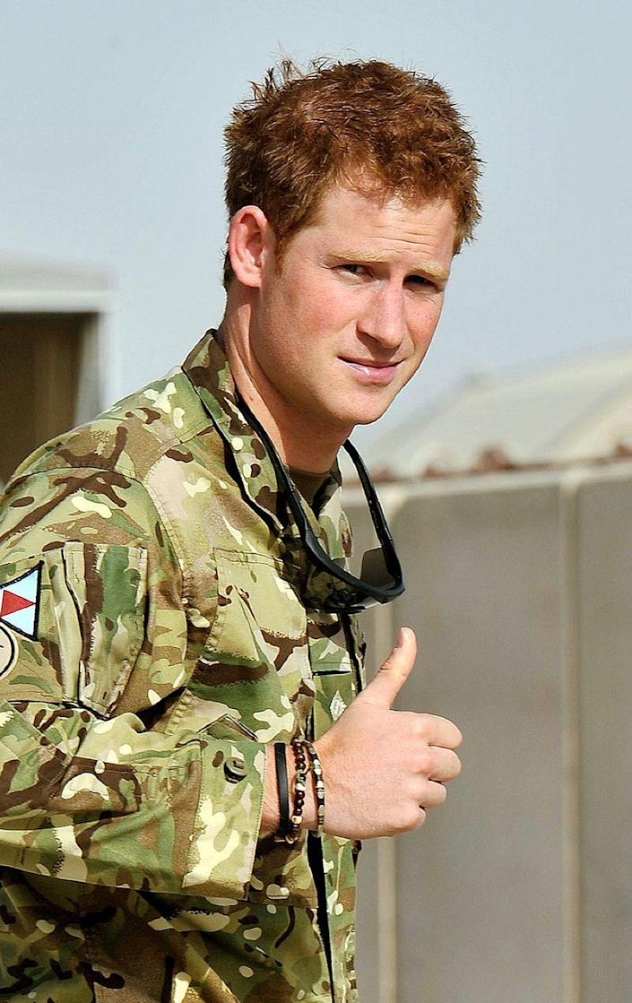 """<p>Harry gives a thumbs up during his second deployment with the Army Air Corps in Afghanistan. In 2013, following the end of his tour, Harry revealed that as commander, he had fired on the Taliban while trying to rescue ground troops. """"My father's always trying to remind me about who I am and stuff like that,"""" he said (via <em><a href=""""https://www.theguardian.com/uk/2013/jan/21/prince-harry-afghanistan"""" rel=""""nofollow noopener"""" target=""""_blank"""" data-ylk=""""slk:The Guardian"""" class=""""link rapid-noclick-resp"""">The Guardian</a></em>). """"But it's very easy to forget about who I am when I am in the army. Everyone's wearing the same uniform and doing the same kind of thing. I get on well with the lads and I enjoy my job. It really is as simple as that.""""</p>"""