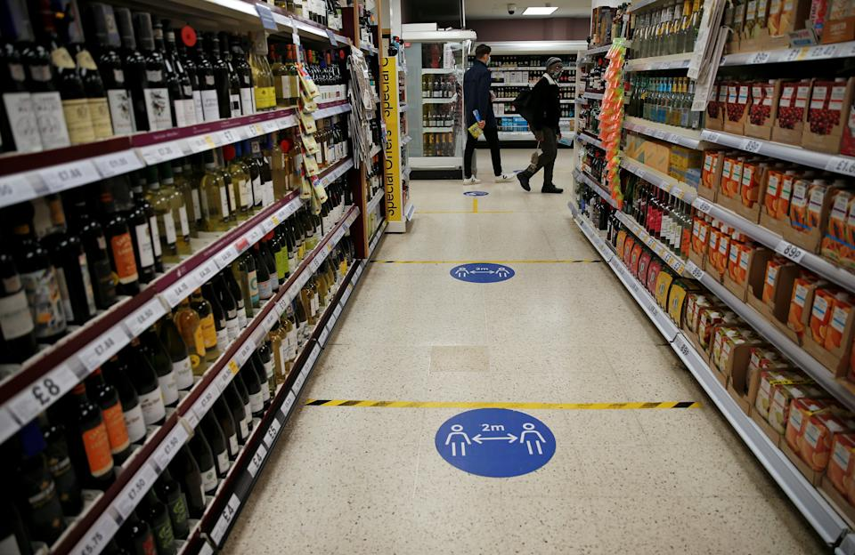 Floor stickers in the alcohol aisle inside a Tesco Metro supermarket ask customers to social distance as they shop, in London on September 23, 2020. - Britain on Tuesday tightened restrictions to stem a surge of coronavirus cases, ordering pubs to close early and advising people to go back to working from home to prevent a second national lockdown. (Photo by Hollie Adams / AFP) (Photo by HOLLIE ADAMS/AFP via Getty Images)