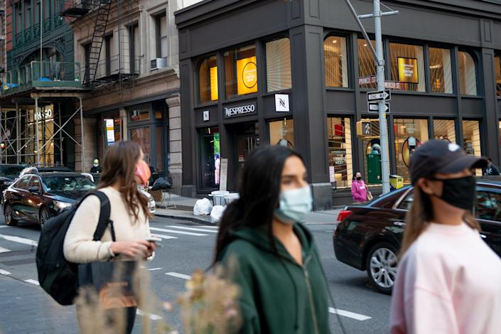 NEW YORK, NEW YORK - SEPTEMBER 22: People wearing masks walk near the Nespresso store in SoHo as the city continues Phase 4 of re-opening following restrictions imposed to slow the spread of coronavirus on September 22, 2020 in New York City. The fourth phase allows outdoor arts and entertainment, sporting events without fans and media production. (Photo by Alexi Rosenfeld/Getty Images)