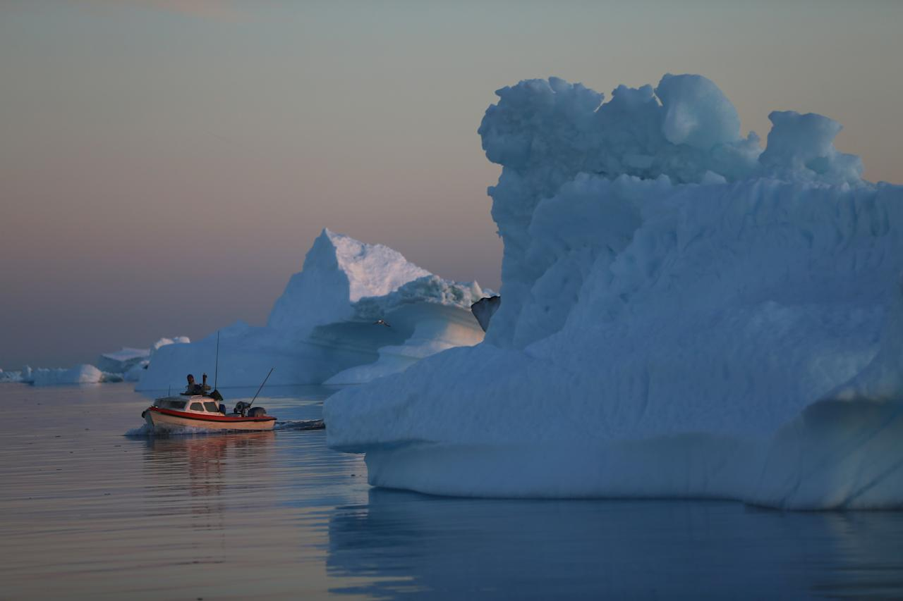 ILULISSAT, GREENLAND - JULY 23: A fishing boat navigates past icebergs that broke off from the Jakobshavn Glacier on July 23, 2013 in Ilulissat, Greenland. As the sea levels around the globe rise, researchers affilitated with the National Science Foundation and other organizations are studying the phenomena of the melting glaciers and its long-term ramifications. The warmer temperatures that have had an effect on the glaciers in Greenland also have altered the ways in which the local populace farm, fish, hunt and even travel across land. In recent years, sea level rise in places such as Miami Beach has led to increased street flooding and prompted leaders such as New York City Mayor Michael Bloomberg to propose a $19.5 billion plan to boost the citys capacity to withstand future extreme weather events by, among other things, devising mechanisms to withstand flooding. (Photo by Joe Raedle/Getty Images)