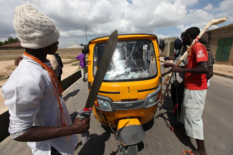"""In this photo taken Wednesday, Aug. 7, 2013. members of the """"Civilian JTF """" with cutlasses and clubs mount a check point on the street of Maiduguri, Nigeria. The battered old car, cutlasses and nail-studded clubs poking out of its windows, careens down the road and squeals to a stop. Its young occupants pile out, shouting with glee, and set up a roadblock. They are part of a vigilante force that has arisen here as a backlash against Boko Haram, the Islamic extremist network responsible for 1,700 deaths in Nigeria since 2010, according to a count by The Associated Press. (AP Photo/Sunday Alamba)"""