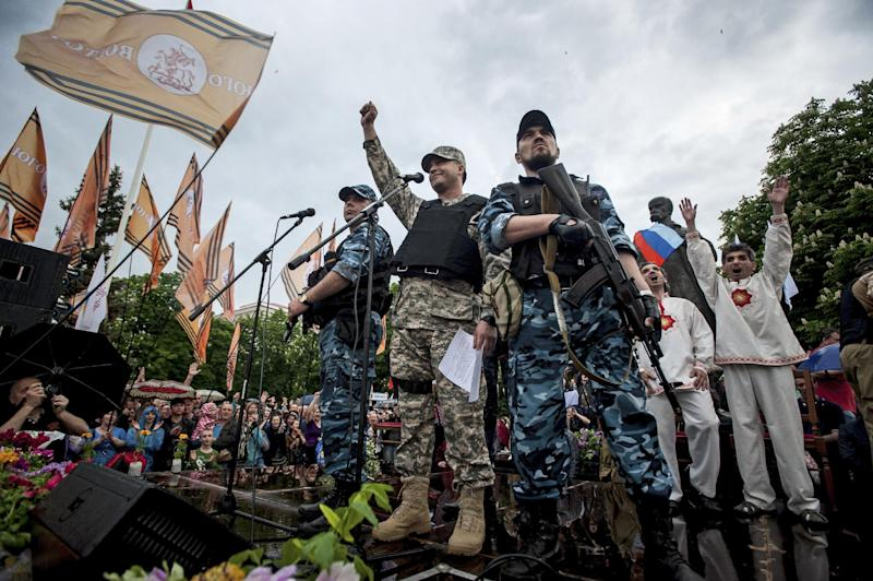 Pro-Russian gunmen and activists react while listening to a speaker as they declare independence for the Luhansk region in eastern Ukraine on Monday, May 12, 2014. Pro-Russia separatists in eastern Ukraine declared independence Monday for the Donetsk and Luhansk regions following their contentious referendum ballot. (AP Photo/Evgeniy Maloletka)