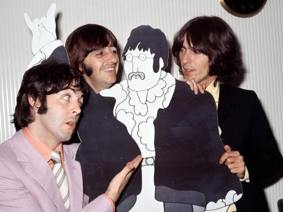 Paul McCartney, Ringo Starr and George Harrison pose with a cardboard John Lennon cut out in his absence in 1968 (Bill Zygmant/Shutterstock)