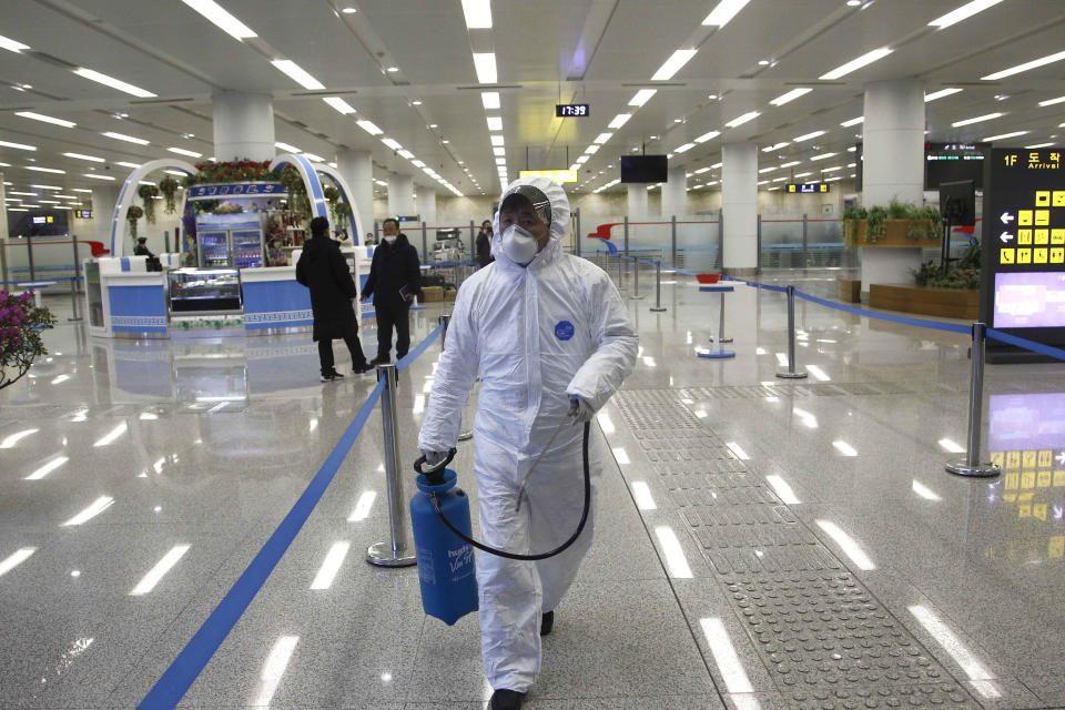 FILE - In this Feb. 1, 2020, file photo, a staff member of State Commission of Quality Management in protective gear carries a disinfectant spray can as they continue to check the health of travelers in foreign countries and inspect and quarantine goods being delivered via the borders at the Pyongyang Airport in Pyongyang, North Korea. A U.N. spokesman said the world body has been left with no international staff in North Korea and its North Korean employees are working remotely. Despite claiming to be coronavirus free, North Korea has sealed off its borders as part of stringent anti-pandemic measures that also involved the departure of diplomats and foreign nationals. (AP Photo/Jon Chol Jin, File)