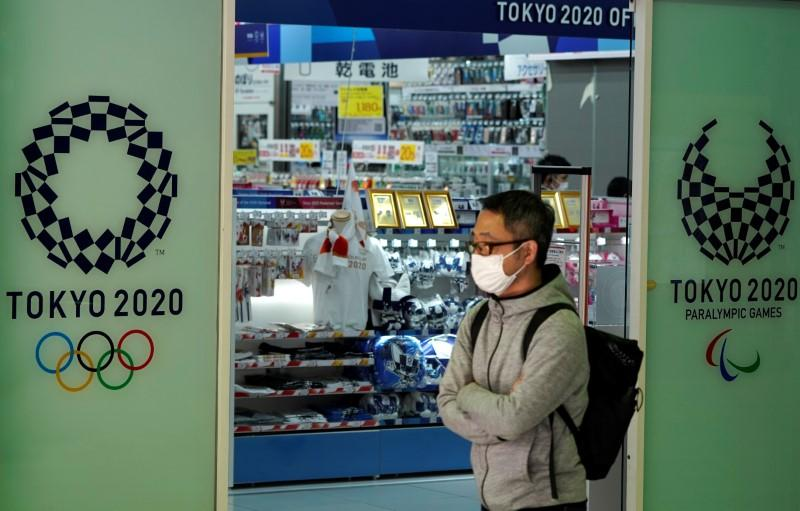 A passerby wearing a protective face mask, following an outbreak of the coronavirus disease, walks past in front of a Tokyo Olympics 2020 souvenir shop in Tokyo, Japan