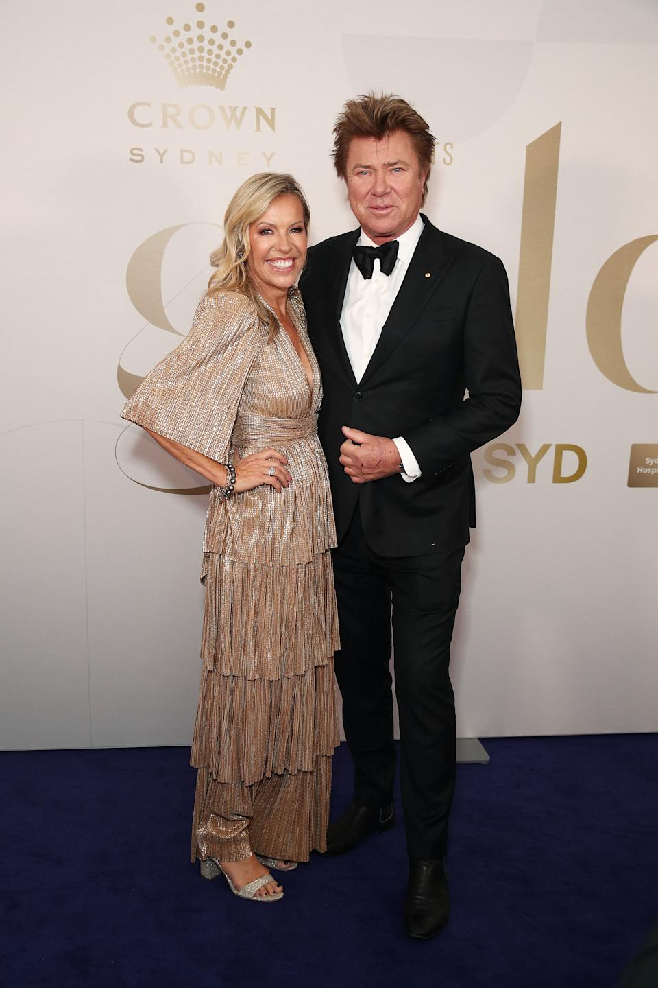 Nicola Dale wears a gold dress and Richard Wilkins wears a black tuxedo at the Gold Dinner 2021 on June 10, 2021 in Sydney, Australia