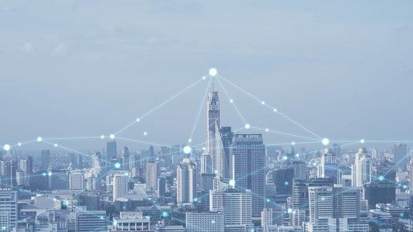 cityscape overlaid with graphic representation of the Internet of Things