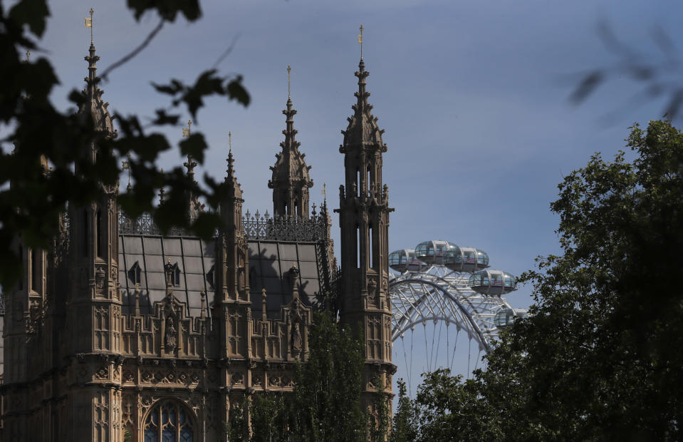 The London Eye stands behind the roof of Parliament in London, Tuesday, June 2, 2020. The British government has decided to scrap a remote-voting system used during the coronavirus pandemic, and has summoned lawmakers back to parliament on Tuesday, but many aren't happy with the arrangements. (AP Photo/Frank Augstein)