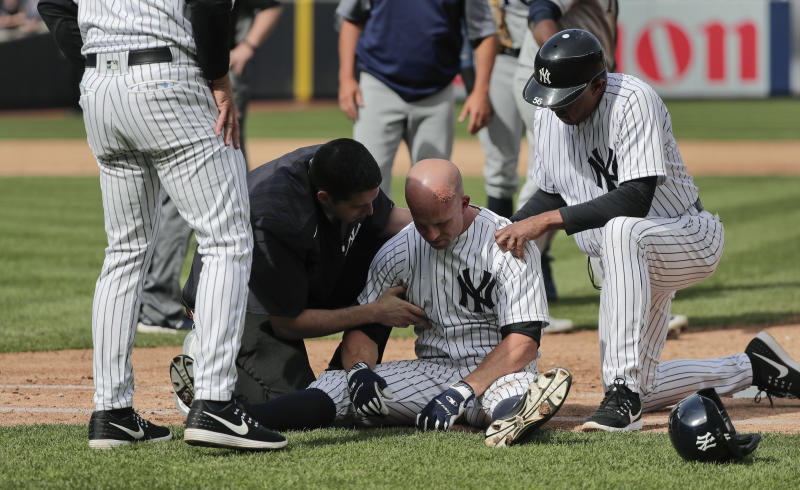 New York Yankees trainers and managers tend to Brett Gardner after Gardner collided with Tampa Bay Rays first baseman Rickie Weeks who was reaching for an errant throw during the sixth inning of a baseball game, Wednesday, April 12, 2017, in New York. (AP Photo/Julie Jacobson)