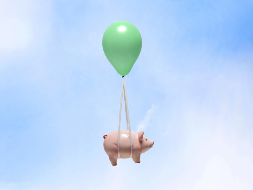 Green helium balloon carrying pink piggy bank with white strings on blue sky.