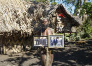 FILE - In this Sunday, May 31, 2015 file photo, Albi Nagia poses with photographs of Prince Philip in Yakel, Tanna island, Vanuatu. A tribe in the remote island nation of Vanuatu who saw Prince Philip as a god will greet his death with ritual wailing and ceremonial dancing, an expert said. The group, based in villages on the island of Tanna in the former Anglo-French colony, revered the Duke of Edinburgh and believed him to be a reincarnation of an ancient warrior who left the island to fight a war. (AP Photo/Nick Perry, File)