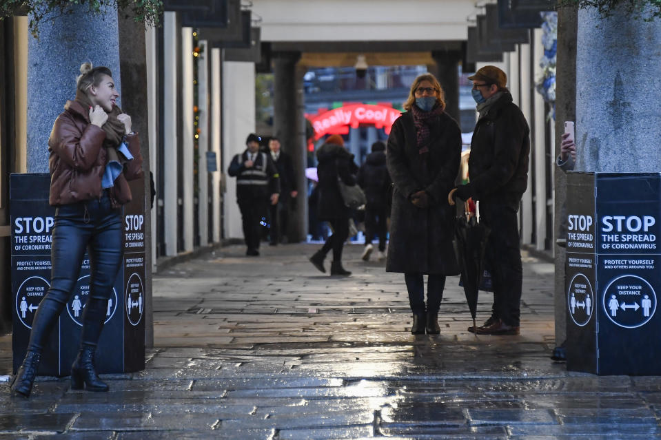 People walking in Covent Garden, London, Thursday, Dec. 3, 2020. Britain became the first country in the world to authorize a rigorously tested COVID-19 vaccine Wednesday and could be dispensing shots within days — a historic step toward eventually ending the outbreak that has killed more than 1.4 million people around the globe. (AP Photo/Alberto Pezzali)
