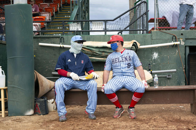 Helena Senators coaches Al Goebel (left) and Anthony Hogan talk near the dugout during the amateur baseball game against the Missoula Mavericks. (Photo by Janie Osborne/Getty Images)