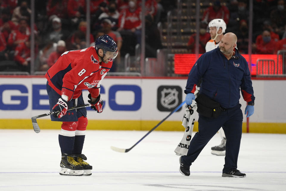 Washington Capitals left wing Alex Ovechkin (8) skates toward the bench next to a trainer after he was injured during the first period of the team's NHL preseason hockey game against the Philadelphia Flyers, Friday, Oct. 8, 2021, in Washington. (AP Photo/Nick Wass)