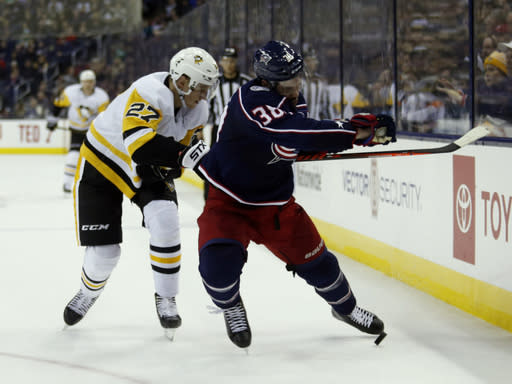 Columbus Blue Jackets forward Boone Jenner, right, chases the puck against Pittsburgh Penguins forward Nick Bjugstad during the first period of an NHL hockey game in Columbus, Ohio, Saturday, March 9, 2019. (AP Photo/Paul Vernon)