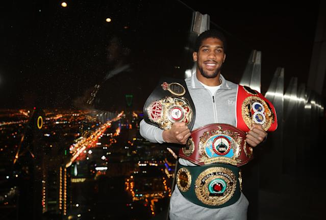 Anthony Joshua poses with his WBA, IBF, WBO and IBO championship belts. (Photo by Nick Potts/PA Images via Getty Images)