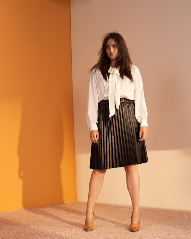 Candice Huffine wears a cream blouse and pleated black skirt from the new Prabal Gurung x Lane Bryant collection. (Photo: Courtesy of Lane Bryant)
