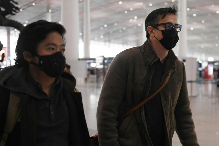 Wall Street Journal reporters Philip Wen (left) and Josh Chin walk through Beijing Capital Airport on their way out of China