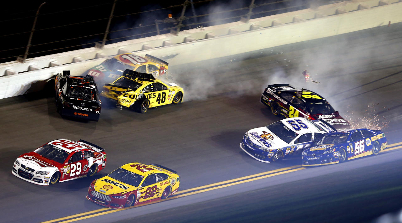 Kevin Harvick (29) and Joey Logano (22) drive away from a wreck involving Denny Hamlin, top left, Jimmie Johnson (48), Kyle Busch (18), Jeff Gordon (24) and Mark Martin (55) in the NASCAR Sprint Unlimited auto race at Daytona International Speedway, Saturday, Feb. 16, 2013, in Daytona Beach, Fla. Marin Truex (56) was able to clear the wreck and continue in the race. (AP Photo/John Moore)