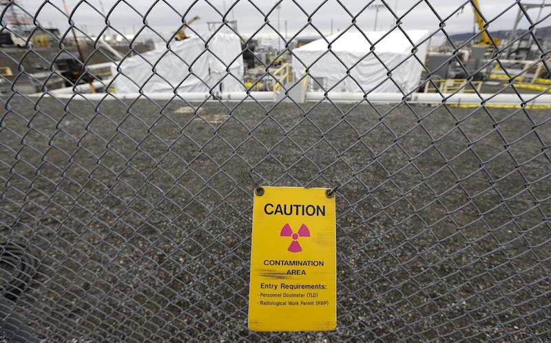 """FILE - In this March 6, 2013 file photo, a warning sign is shown attached to a fence at the 'C' Tank Farm at the Hanford Nuclear Reservation, near Richland, Wash. Documents obtained by the Associated Press show that there are """"significant construction flaws"""" in some newer, double-walled storage tanks at the nuclear waste complex. (AP Photo/Ted S. Warren, File)"""