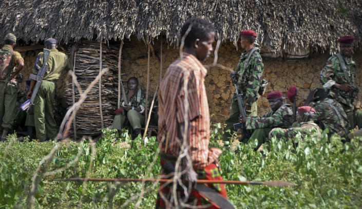 A villager armed with a spear walks past Kenyan police sent to keep order following tribal clashes in Kipao village in the Tana River Delta region of southeastern Kenya Friday, Dec. 21, 2012. At least 39 people including men, women, children, and attackers, were killed when farmers from the Pokomo tribe, armed with spears and AK-47 rifles, raided a village of semi-nomadic Orma herders early Friday in renewed fighting between two communities with a history of violent animosity, a police official said. (AP Photo)