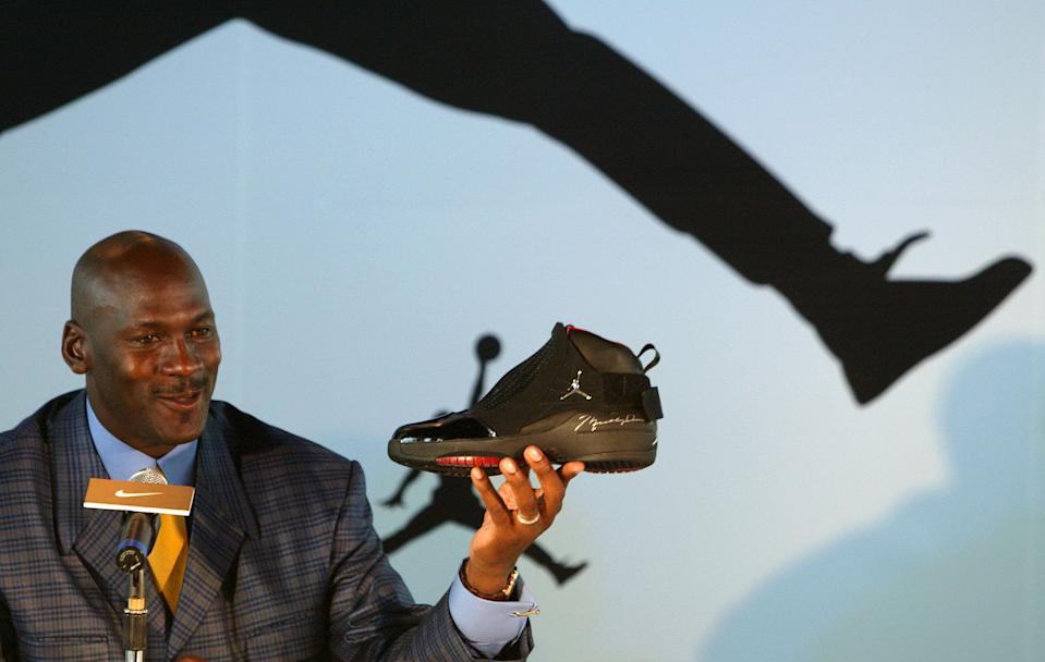 U.S. basketball legend Michael Jordan displays a shoe during a news conference in Hong Kong May 21, 2004. (Photo: REUTERS/Bobby Yip BY/TW)