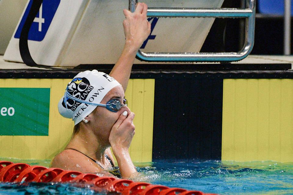 Kaylee McKeown reacts after setting a new world record time in the women's 100m backstrokeat the Australian Olympic swimming trials.